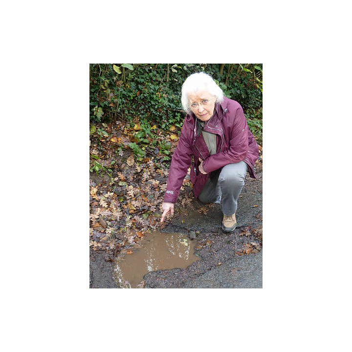 Cllr Gill Moseley points out a pothole that urgently needs repair by Gloucestershire County Council